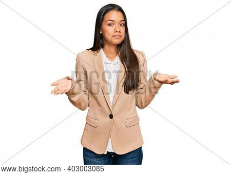 Beautiful hispanic woman wearing business jacket clueless and confused expression with arms and hands raised. doubt concept.
