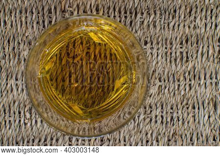 Top View Of A Glass With Whiskey Standing On A Wicker Base. View Of A Wicker Mat Through A Transpare