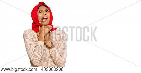 Young african american woman wearing traditional islamic hijab scarf shouting suffocate because painful strangle. health problem. asphyxiate and suicide concept.