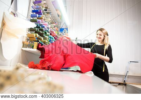 Young Dressmaker Woman Sews Clothes On Sewing Machine.