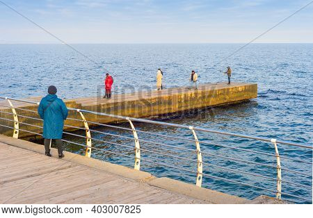Odessa, Ukraine - November 26, 2020: People On A Pier In Fron Of The Balck Sea In Odessa In A Sunny