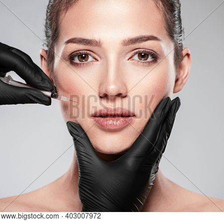 Young caucasian woman getting cosmetic injection near the eyes. Beautiful woman gets  injection in her face. Adult girl gets cosmetic injection of botox in a clinic. Beauty treatments