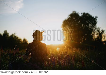 Silhouette Of Woman Relaxing In Lupine Field In Sunset. Atmospheric Moment In Summer Countryside