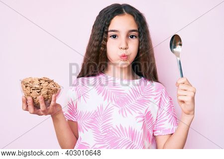 Cute hispanic girl holding cornflakes and spoon puffing cheeks with funny face. mouth inflated with air, catching air.