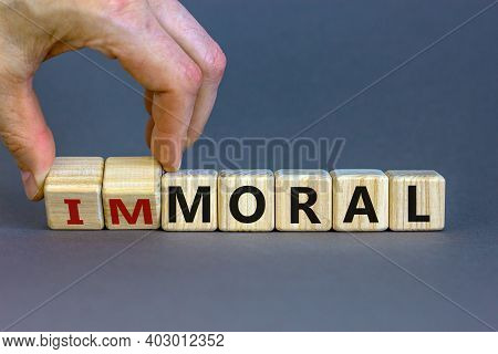 Moral Or Immoral Symbol. Hand Turns Cubes And Changes The Word 'immoral' To 'moral'. Beautiful Grey