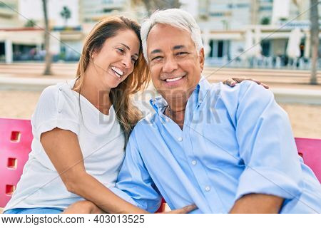 Middle age hispanic couple smiling happy and hugging sitting on bench at the beach.