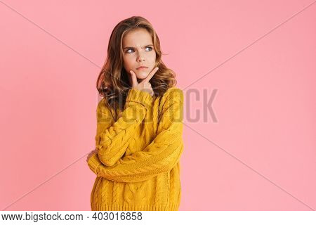 Perplexed beautiful blonde girl thinking and looking aside isolated over pink background