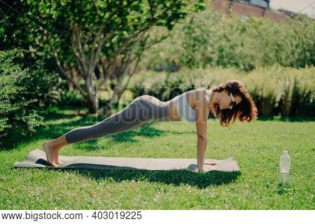 Photo Of Pretty Fit Woman Poses Full Length In Plank Pose Dressed In Cropped Top And Leggings Poses