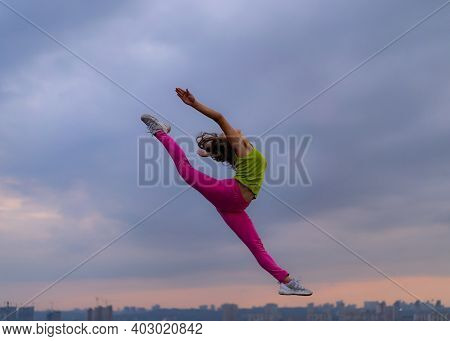 Silhouette Of Flexible Woman Jumping On The Dramatic Cloudscape During Sunset. Concept Of Excitement