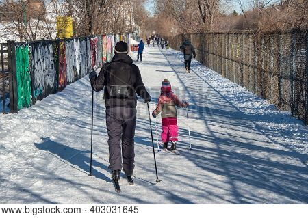 Montreal, Ca - 6 January 2021: Father And Young Daugther Skiing After Snowfall On The Path Of Chemin