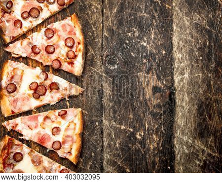 Pizza With Meat Sausages And Cheese. On A Wooden Background