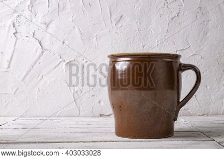 A Clay Pot Against A White Wall. Old Accessories In The Household.