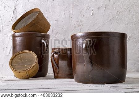 A Clay Pot And A Wooden Strainer On A White Wall Background. Old Accessories In The Household.