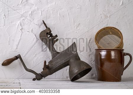 A Clay Pot, A Wooden Strainer And A Metal Device For Juicing Against A White Wall. Old Accessories I