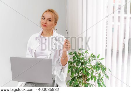 A Blonde Doctor In Glasses Or A Cosmetologist In A White Coat Is Sitting At A Computer. She Reads An