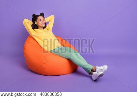 Full Size Photo Of Optimistic Girl Lying On Pouf Look Empty Space Wear Yellow Shirt Trousers Sneaker