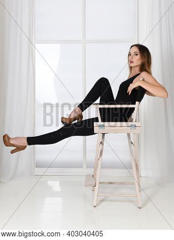 Fashion Pose - Woman Sits On Chair In Model Pose In High Heels