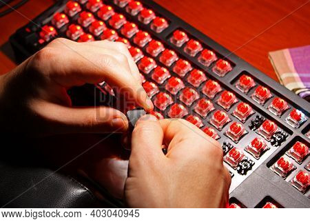 Man Is Holding In Hands Black Keyboard Button. Glowing Red Keyboard Switches. Gaming Mechanical Comp