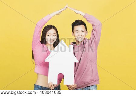 Happy Young Couple Holding A Small House The In Their Hands. Family And House Concept