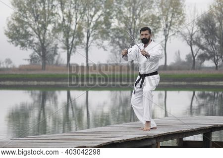 The Man In White Kimono Is Practicing Martial Arts With Sai Weapons Outdoors On Lakeshore In Nature.