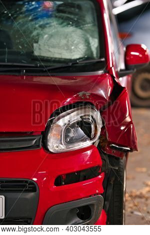 Red car with damaged front bumper and headlamp, deployed airbag