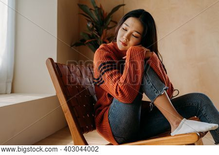 Depressed Sad Girl Feeling Lonely Sitting By Home Winter Looking Out The Window In Winter. Asian Wom