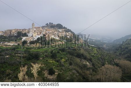 Foggy morning at the hill of Polop de Marina with church and castell over green forest at the Costa Blanca, Spain