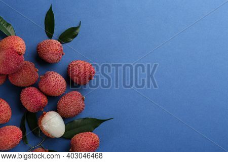 Fresh Ripe Lychees With Leaves On Blue Background, Flat Lay. Space For Text