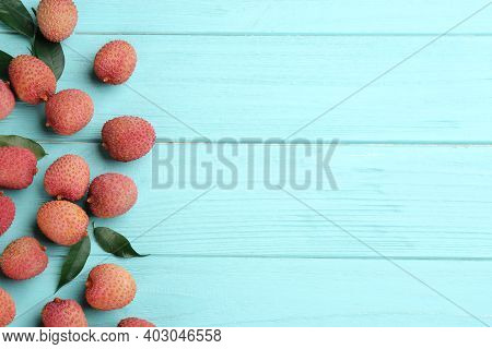 Fresh Ripe Lychee Fruits On Light Blue Wooden Table, Flat Lay. Space For Text
