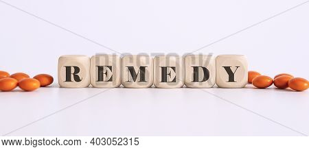 Top View Blocks With Word Remedy On The White Background With Pills
