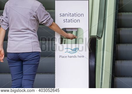 Close-up View Of Woman Sanitizing Her Hands At Sanitation Station Outside A Shopping Mall
