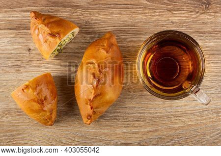 Whole Small Pie, Halves Of Pie With Green Onion And Egg, Transparent Cup With Tea On Wooden Table. T