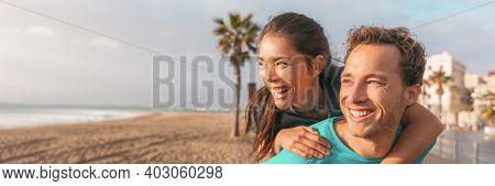 Happy couple having fun laughing on beach banner. Portrait of young Asian woman piggybacking on male boyfriend outside panoramic.