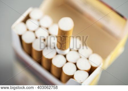 Open Pack Of Cigarettes With One Stretched Out Cigarette Close-up.