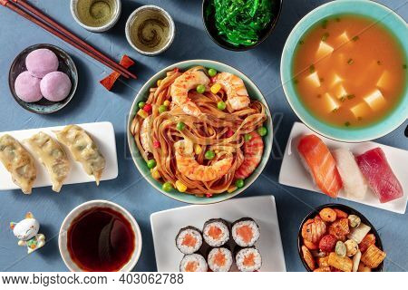 Japanese Cuisine. Sushi, Udon, Miso Soup, Tea, Mochi Etc, Shot From Above On A Blue Background