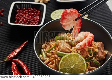 Pad Thai. Stir-fried rice noodles with chicken meat, shrimps,  scrambled egg, peanuts, vegetables and sauce in bowl. Thai food. Setting table.