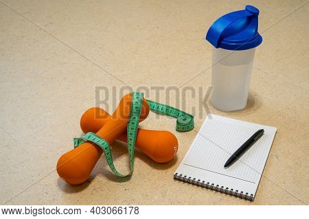 Fitness Background. A Set Of Accessories For Training At Home During Quarantine - A Pair Of Dumbbell