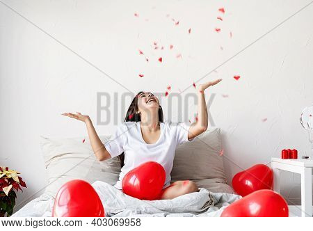 Young Happy Brunette Woman Sitting In The Bed With Red Heart Shaped Balloons Throwing Confetti In Th