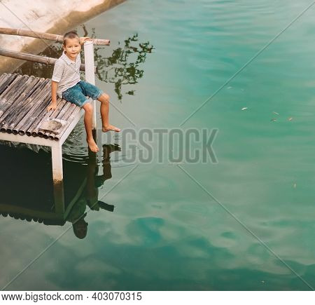 Outdoor portrait of a little cute boy sitting on a jetty of a lake