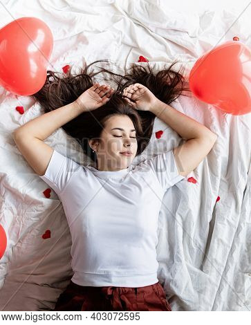Young Happy Brunette Woman Laying In The Bed With Red Heart Shaped Balloons And Decorations