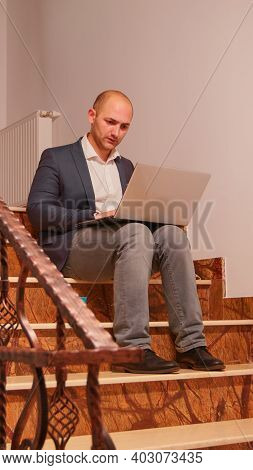 Exhausted Businessman Using Laptop Working Alone On Difficult Deadline Sitting On Stair Overtime. Ex