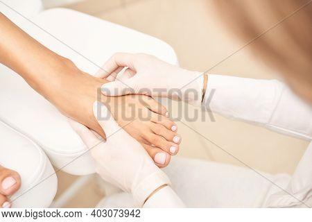 Pedicure Nail Spa Procedure. Foot Manicure. Salon Master. Polish Woman Leg. Hands In Gloves. Light B