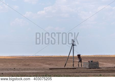 Transformer Station Near A Pillar In Steppe. Rural Power Lines. Electric Generators Connected To Lin