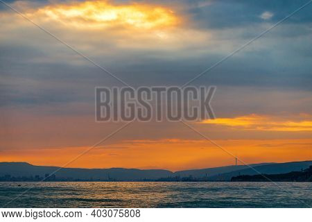 Cargo Ship Sailing The Sea At A Golden Sunset Or Sunrise. Ocean Shipment Across Water As The Sun Set
