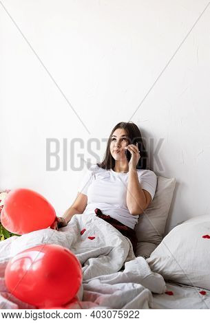 Young Brunette Woman Sitting Awake In The Bed With Red Heart Shaped Balloons And Decorations Texting