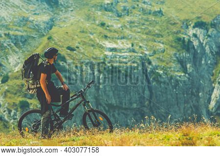 Caucasian Biker In His 30s On The Scenic Mountain Biking Trail. Summer Time Recreation Theme.