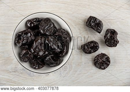 Dried Black Plums In White Bowl, Few Prunes On Wooden Table. Top View