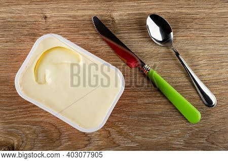 White Plastic Box With Creamy Cheese, Table Knife With Green Handle, Teaspoon On Brown Wooden Table.