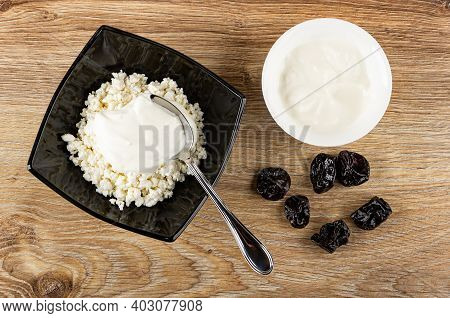 Spoon In Black Glass Bowl With Defatted Grainy Cottage Cheese And Sour Cream, White Bowl With Sour C