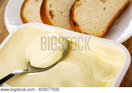 Close Up Of Teaspoon In Plastic Box With Creamy Cheese, Slices Of Bread With Raisin In Plate On Wood